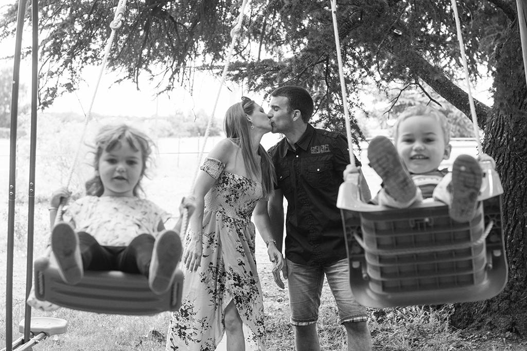 séance photo famille à domicile enfants portrait Toulouse lauragais balançoire jeux baiser bisous parents